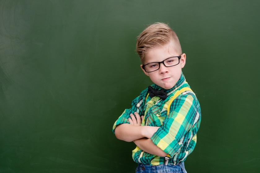 Funny angry nerd near empty green chalkboard